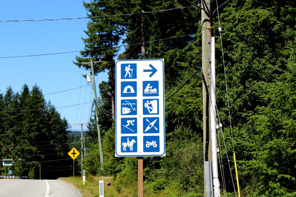 A road sign points right, indicating opportunities for camping, climbing, kayaking, skiing and more