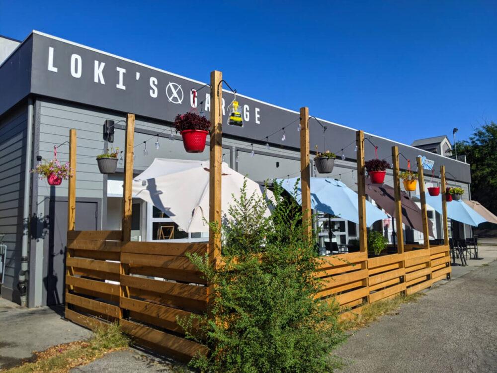 Grey Loki's Garage building with wooden patio and umbrellas