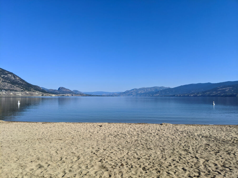 Sandy beach in front of calm lake, lined by rolling hills