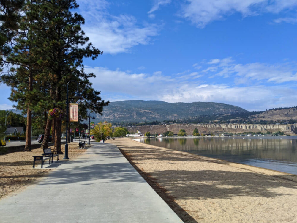 Concrete walking path next to sandy beach and calm lake in Penticton