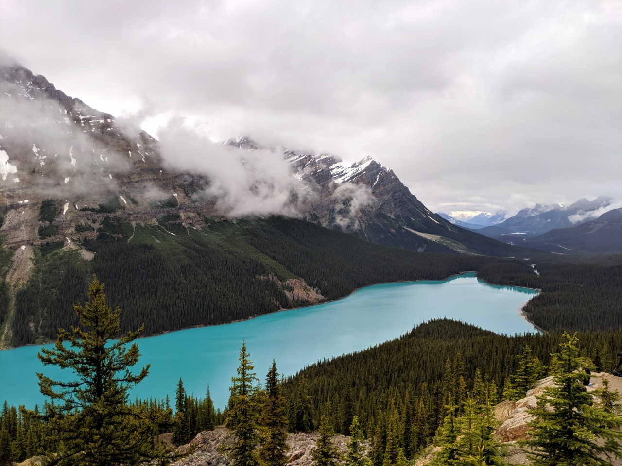 Turquoise lake with mist and snow capped mountains