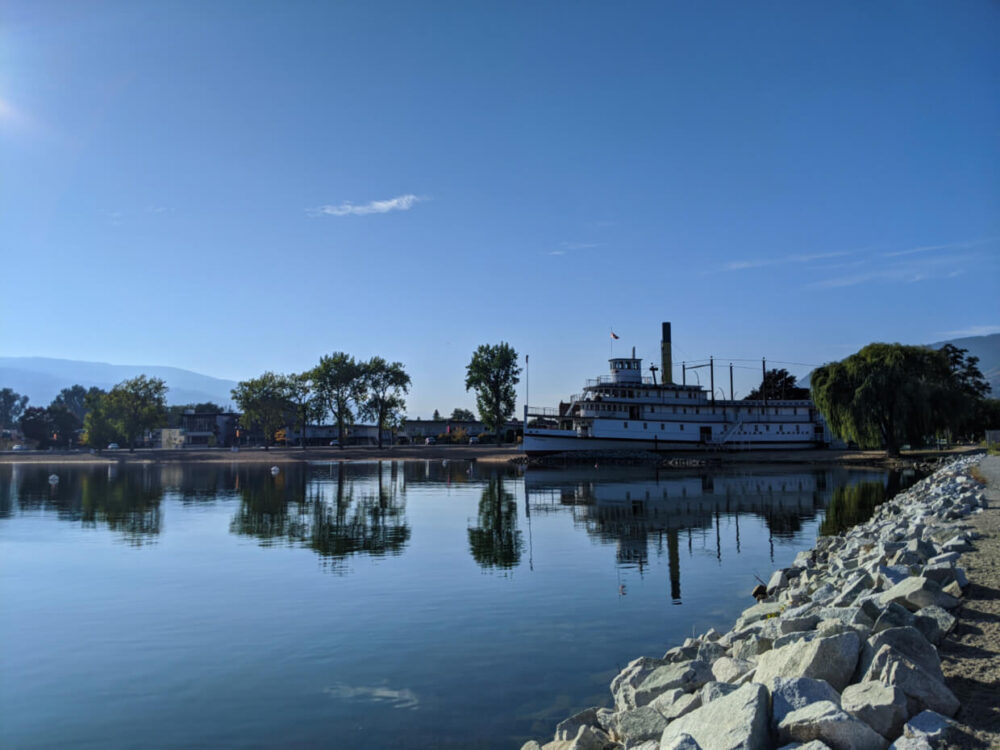 View of SS Sicamous sternwheeler boat on calm lake with reflections