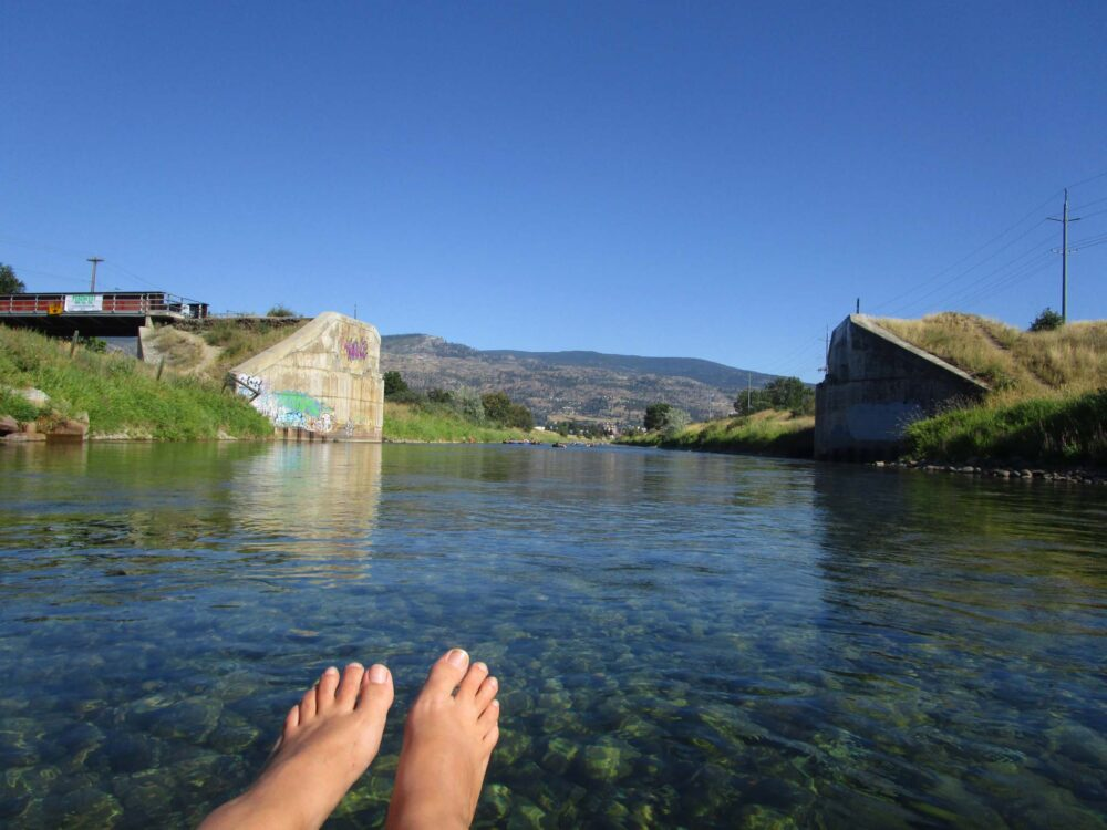 Feet with clear water and blue skies while floating the Penticton Channel