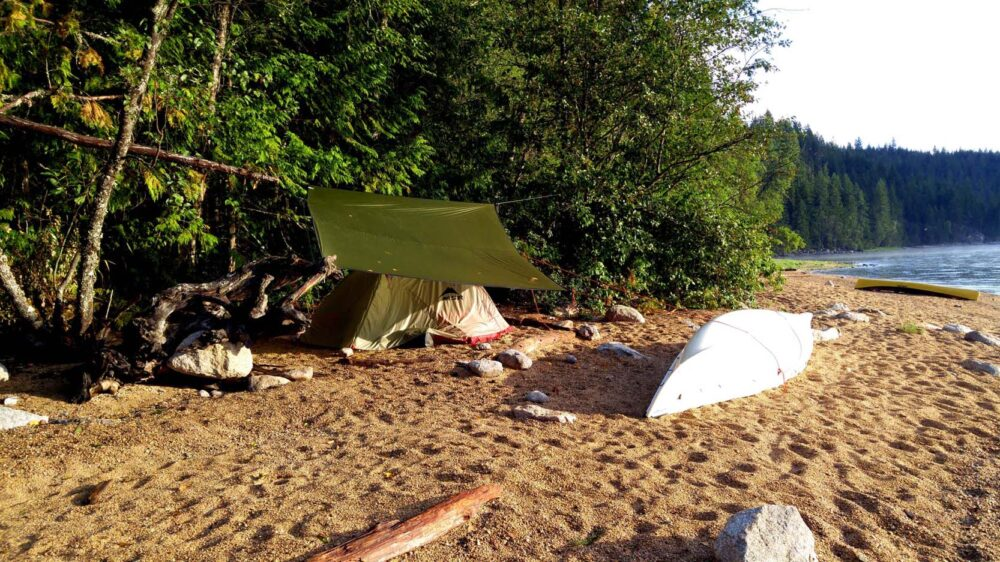 Tarp, tent and canoe on sandy beach next to lake