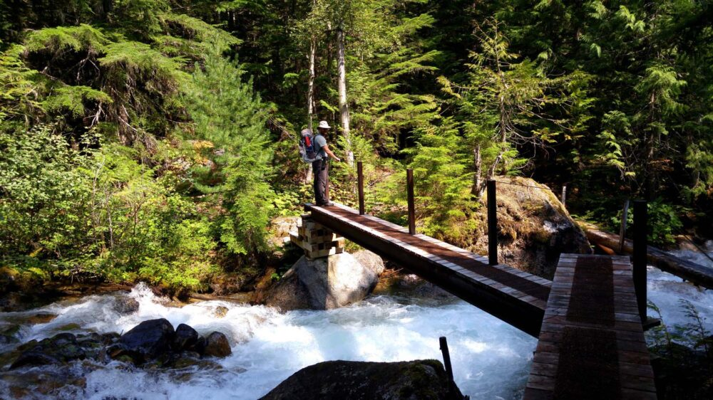 Crossing a wooden bridge above a raging river, Valhalla Provincial Park