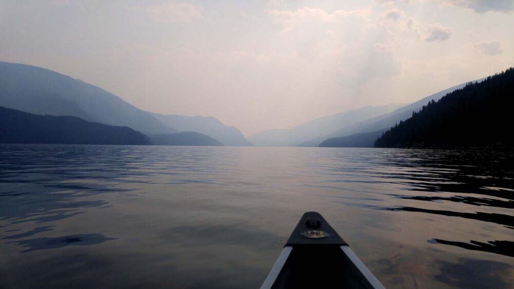 Smoky skies above the deep lake with canoe in front
