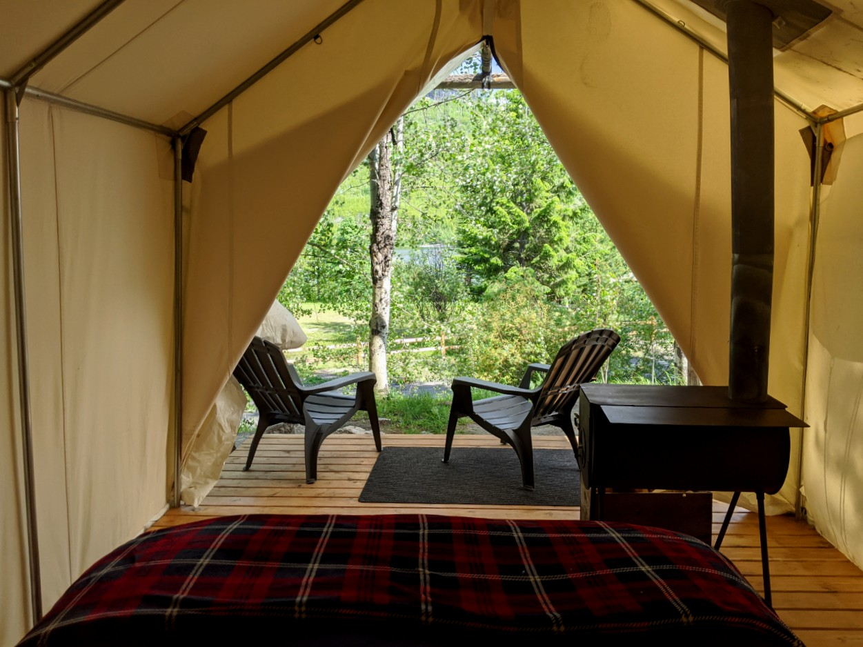 Looking from the bed outside in one of Chute Lake Lodge's Glamping tents, with wood stove and chairs on deck
