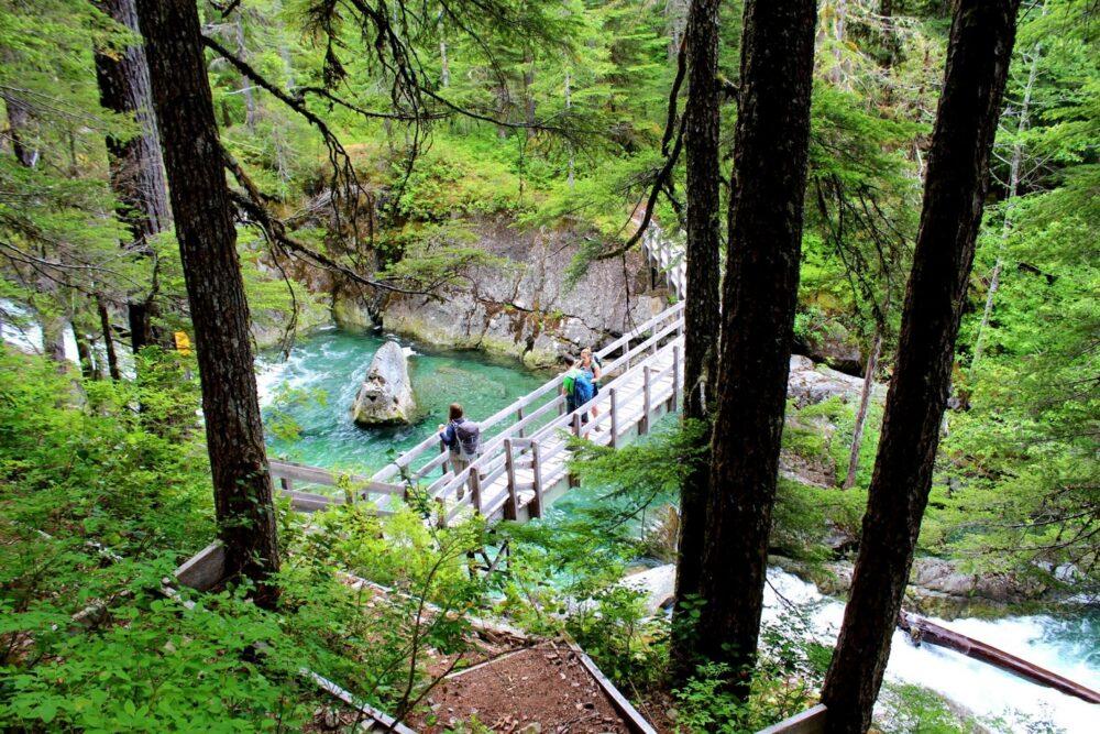 Three hikers on bridge over turquoise river, Della Falls trail