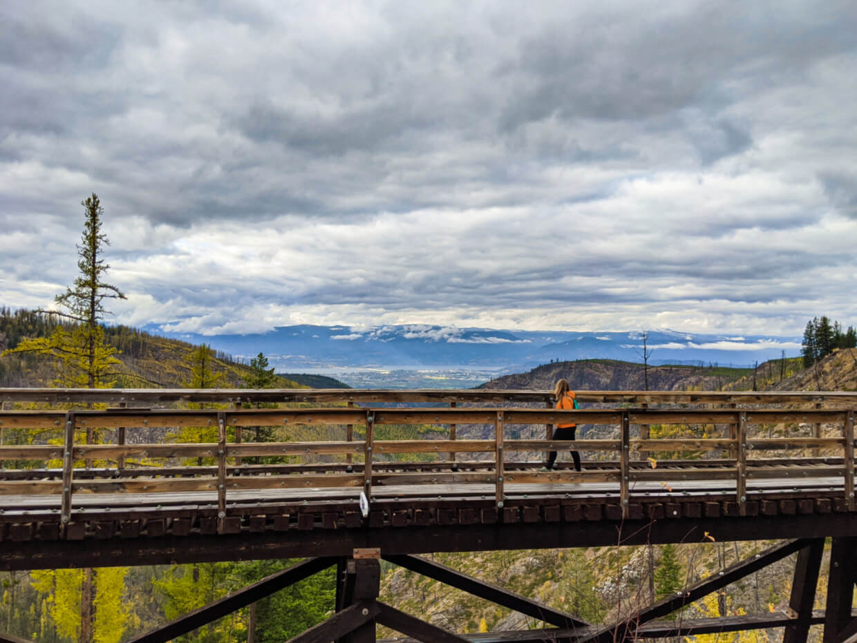 Gemma crossing one of the wooden trestles in Myra Canyon with views of Kelowna in background