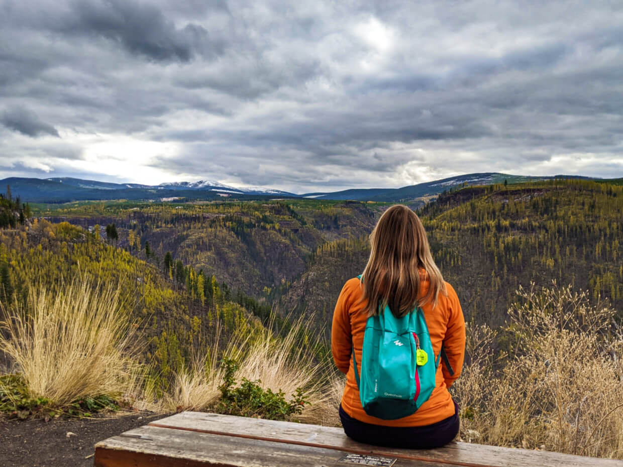 Gemma sat on bench looking out to views in Myra Canyon