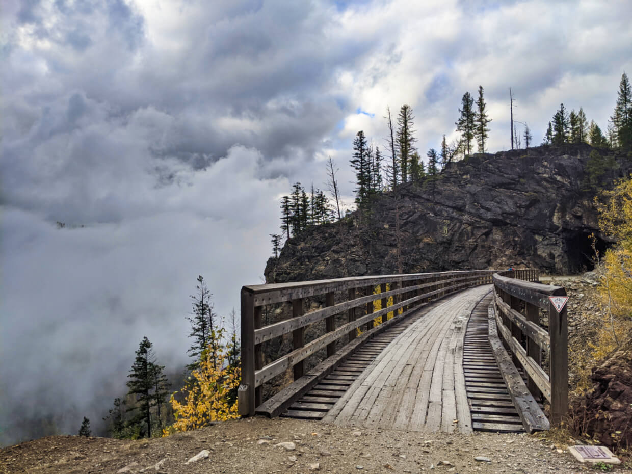Trestle bridge leading away from camera towards rock tunnel with fog behind