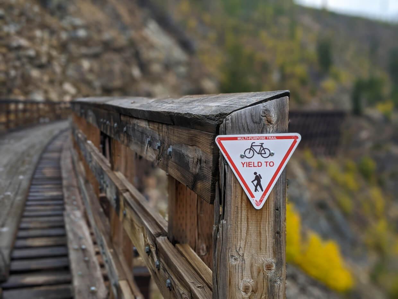 Close up of multi-purpose trail sign on wooden trestle bridge