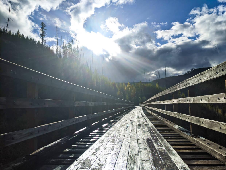 Sunbeams through clouds on wet trestle bridge in Myra Canyon