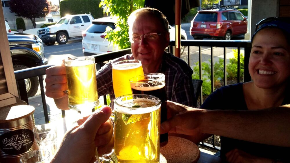 Four people clinking glasses on brewery patio in Penticton