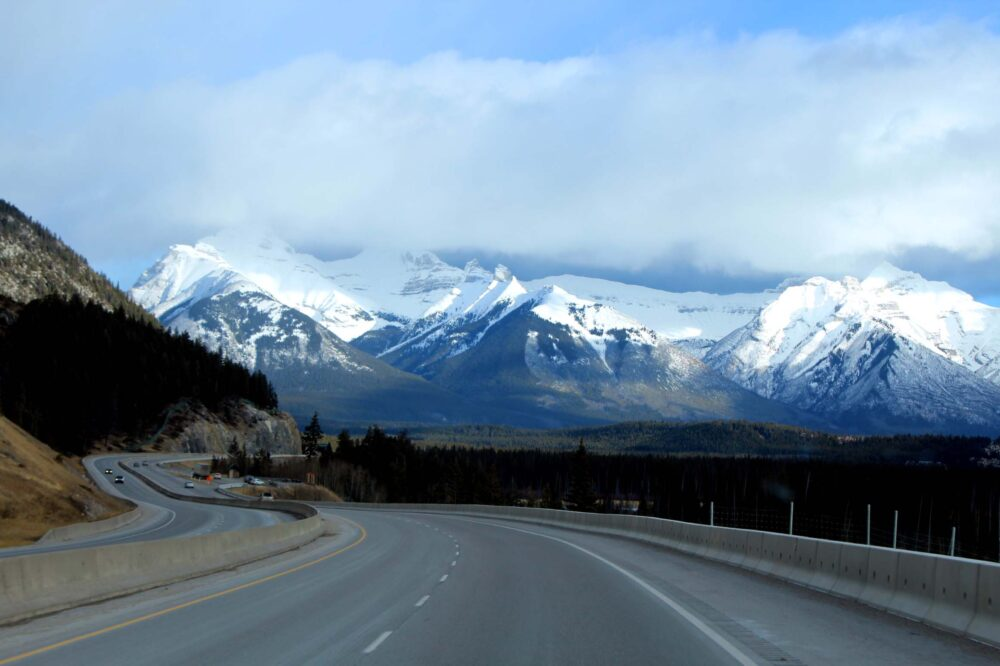 A highway snakes between snow capped mountains