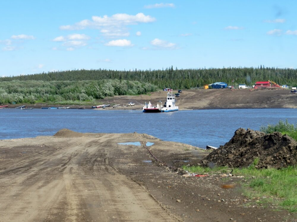 Dirt track leads to river, with ferry on the other side