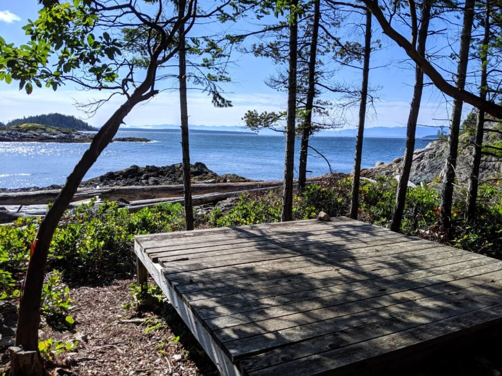 Wooden tent pad in front of coastal scenic view of mountains and islands