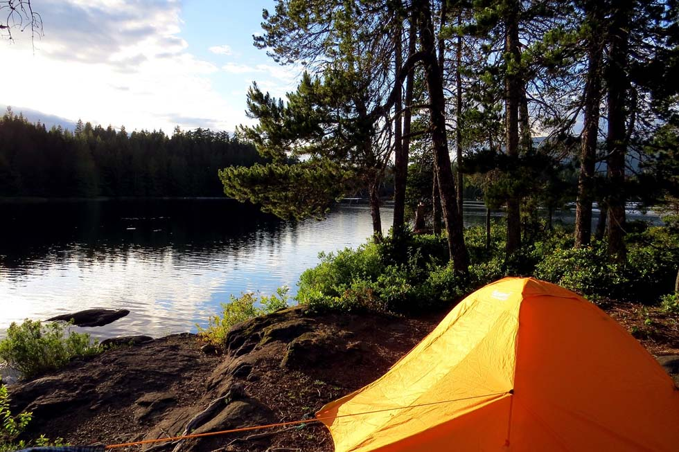 Orange tent set up on island next to lake, with a backdrop of trees
