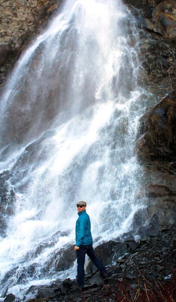 JR standing in front of high cascading waterfall