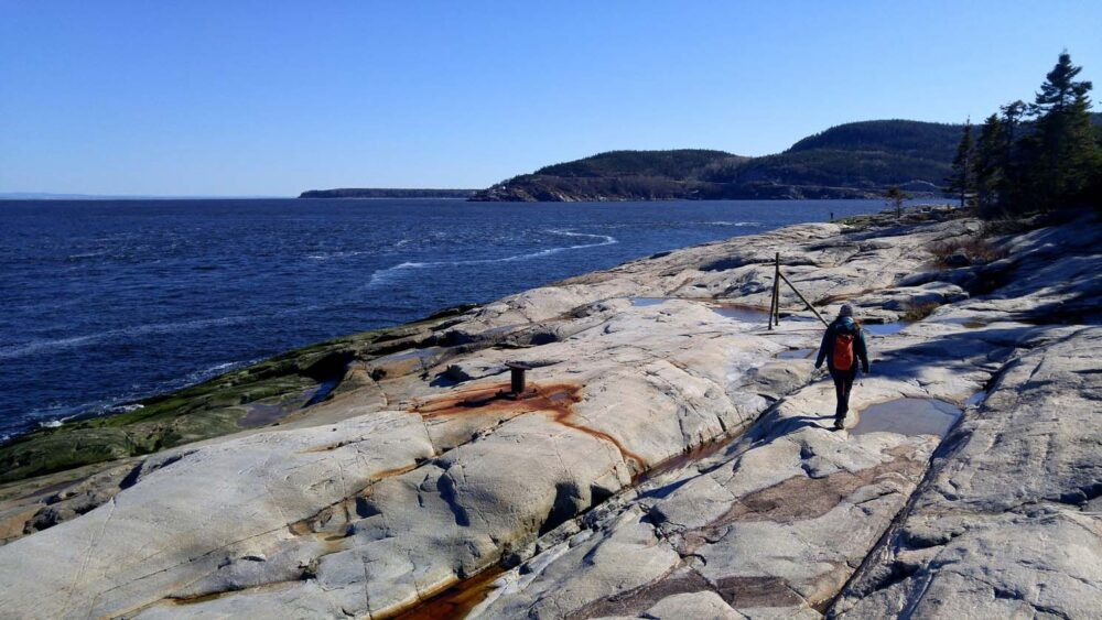 Gemma walking along rocky shoreline in Tadoussac, Quebec