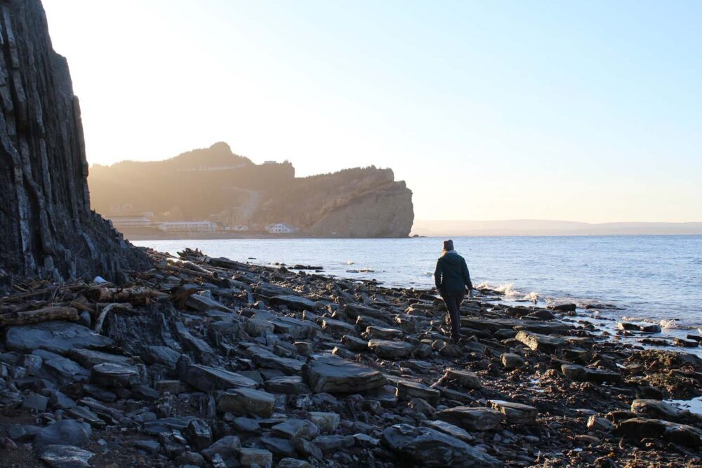 Gemma walking on rocky beach at sunset at Perce, Gaspe Peninsula