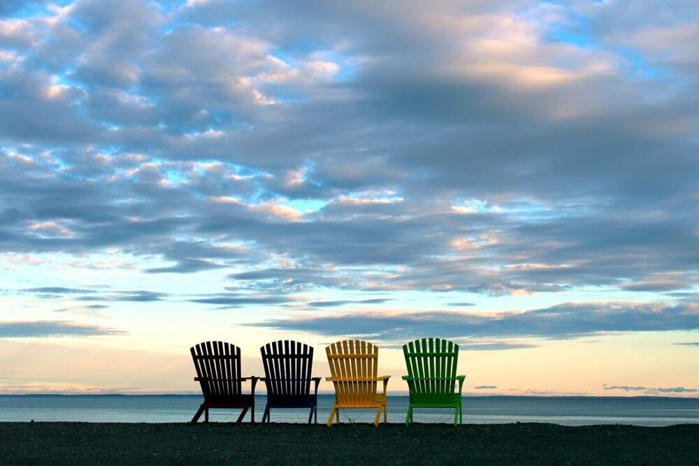 Backview of four colourful oversize beach chairs  on beach looking out to ocean