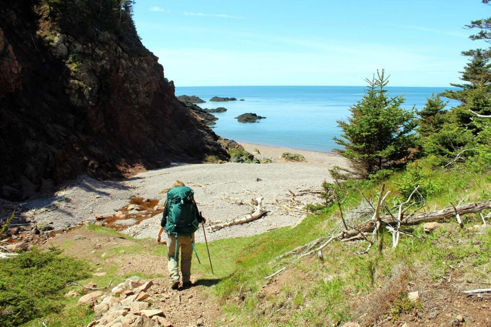Gemma approaching sandy beach on the Cape Chignecto Trail, an ideal multi-day hike to do in Canada in spring