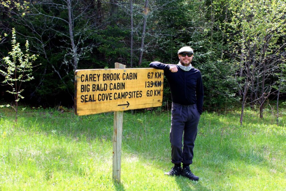 JR standing next to Cape Chignecto Coastal Trail sign with distances to cabins and campsites