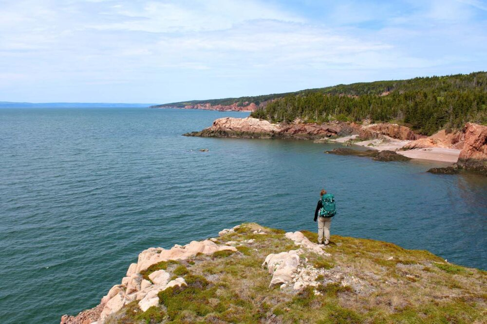 Gemma standing on rocky headland looking back at Nova Scotia coastline on the Cape Chignecto Trail