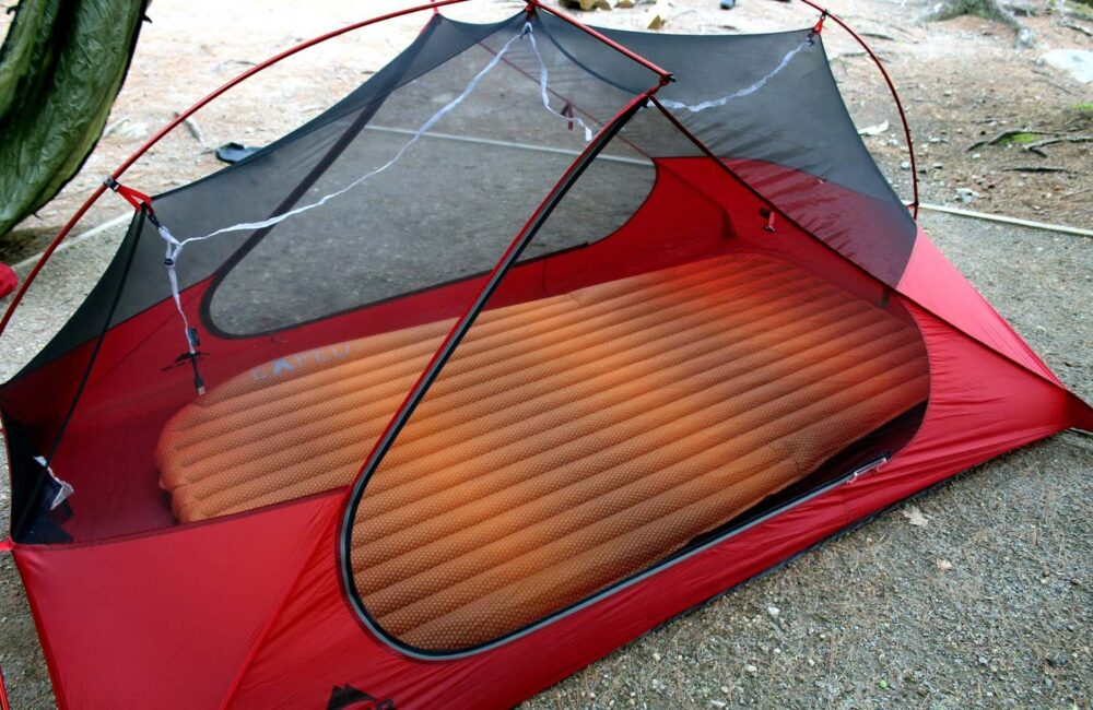 Small red tent set up on ground with  inflated orange sleeping mat visible through mesh