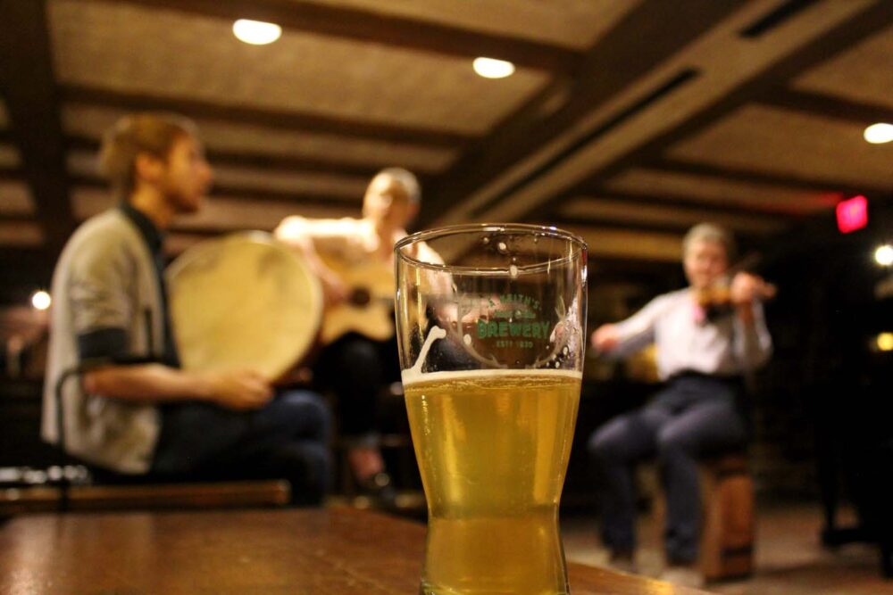 Glass of beer with blurred musicians in background
