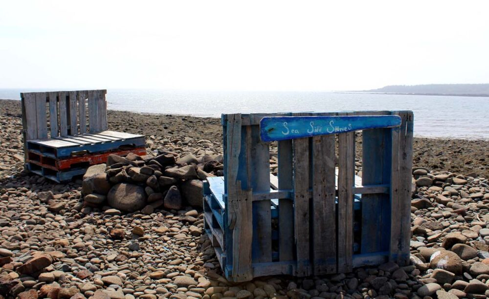 Wooden pallet chairs on rocky Pond Cove Beach, Brier Island