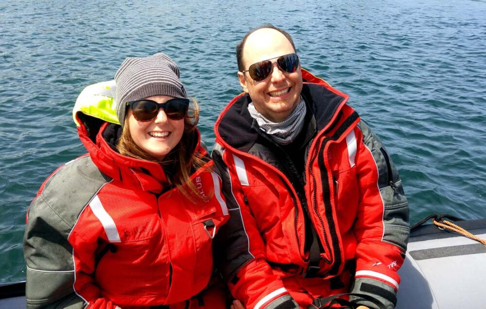 Gemma and JR sat on Zodiac boat wearing red flotation suits