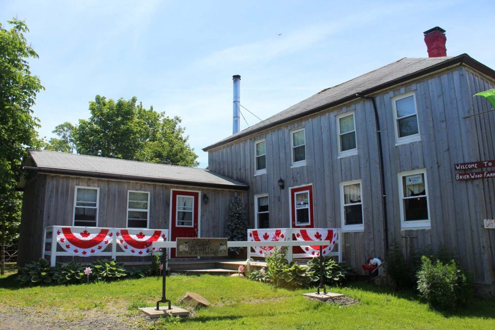 Two story 19th century farmhouse with Canadian flags outside