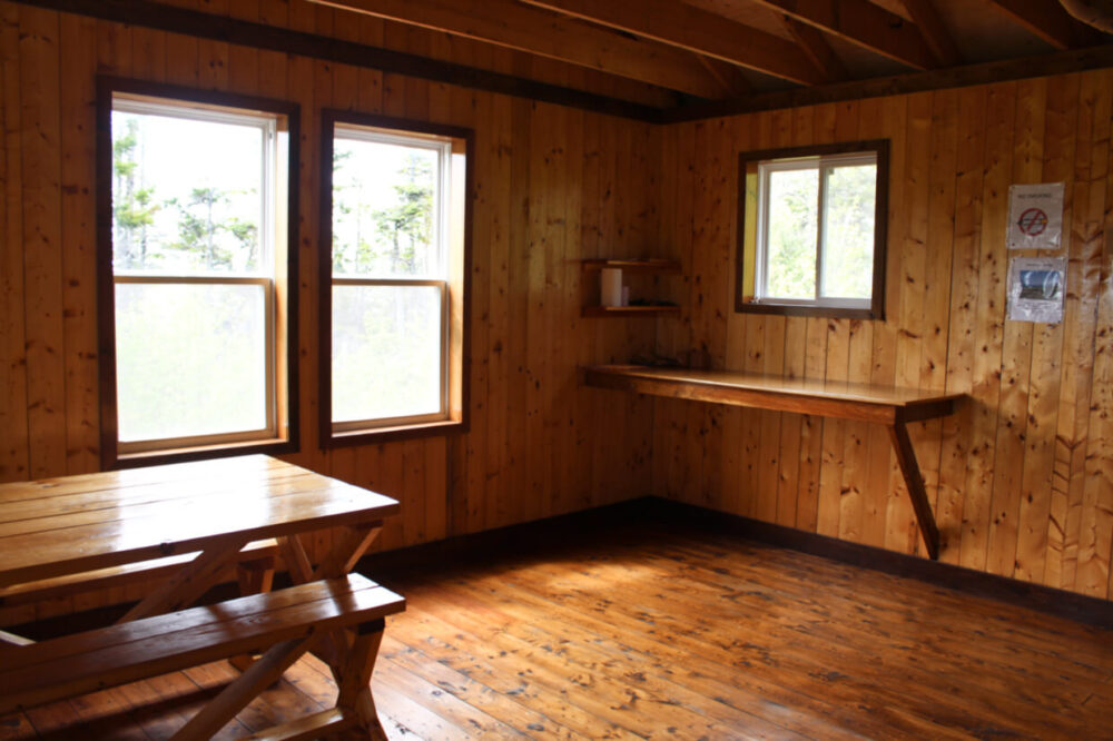 Inside the Big Bald Cabin, with wooden walls, wooden shelf, wooden picnic table and three windows