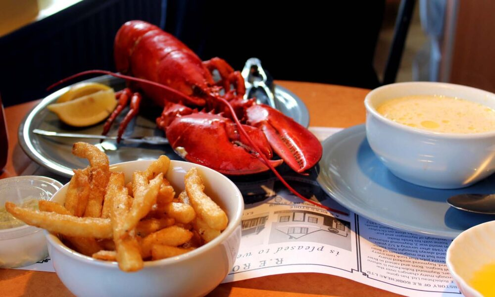 Cooked lobster, fries and clam chowder soup on table