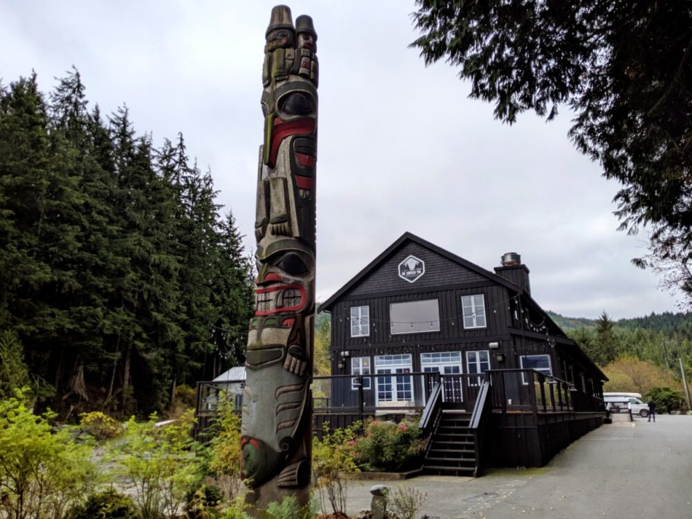 Painted totem pole in front of cafe restaurant in Port Renfrew on the Pacific Circle Marine Route