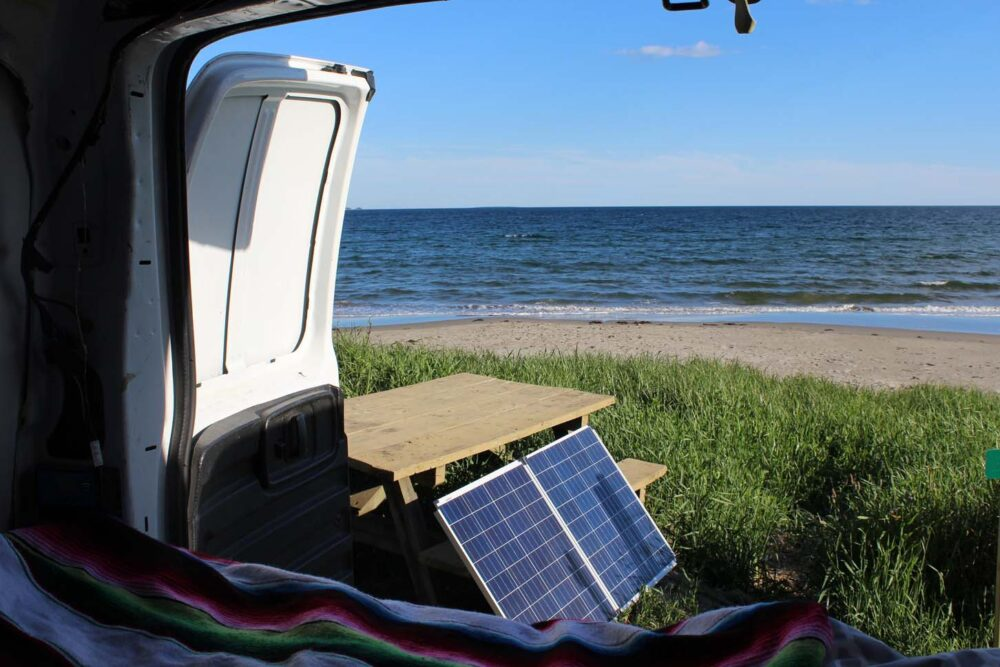 Looking out the back doors of our converted van, to picnic table with solar panels resting on it, with sand beach and ocean in background