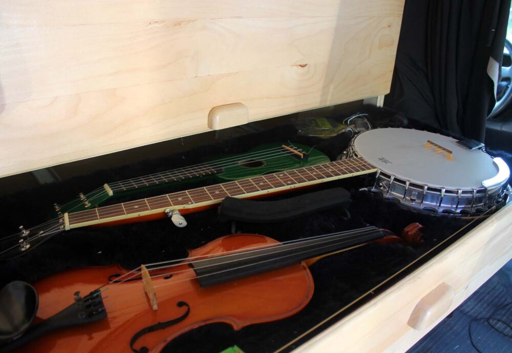 open music drawer in gmc savana diy conversion van with banjo, violin and ukulele