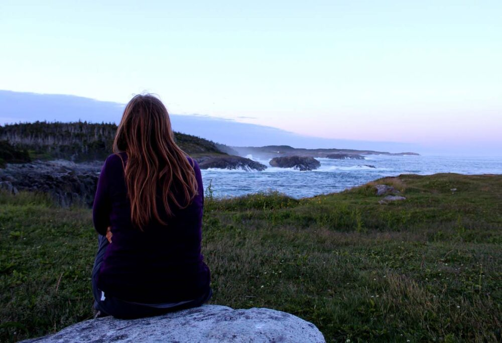Gemma sat in front of Louisbourg Lighthouse coastline