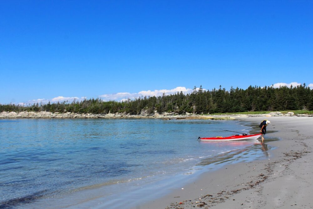 JR pulling his red kayak onto the shore on the Borgles Island sandbar