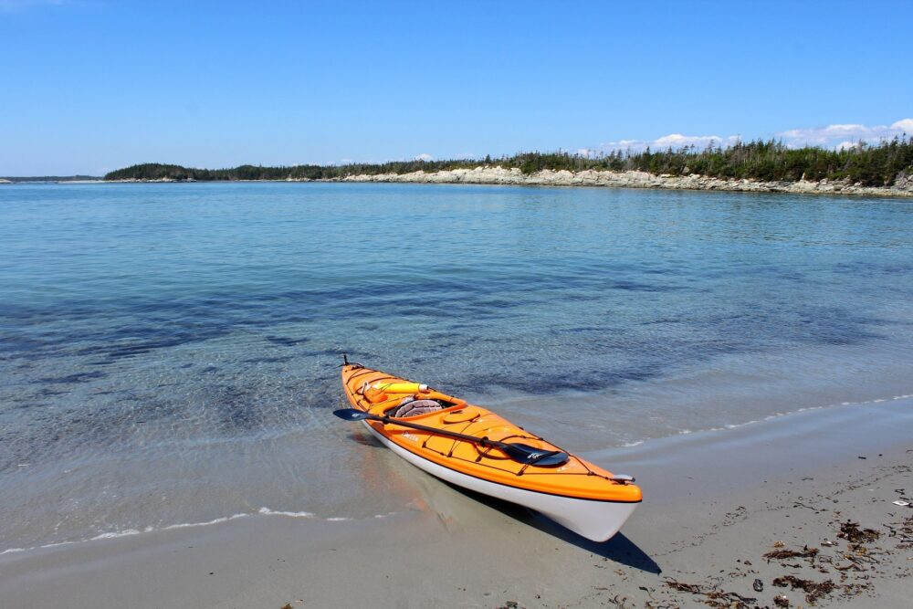 Orange kayak on beach with aquamarine ocean, Nova Scotia, Canada