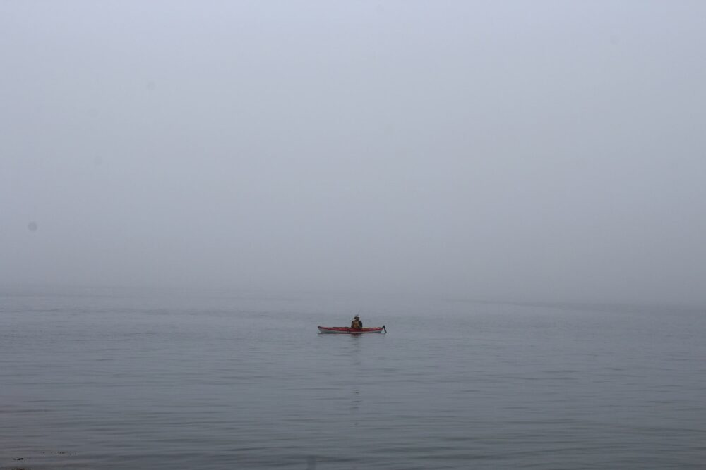 A red kayak floats on a calm ocean surrounded by fog