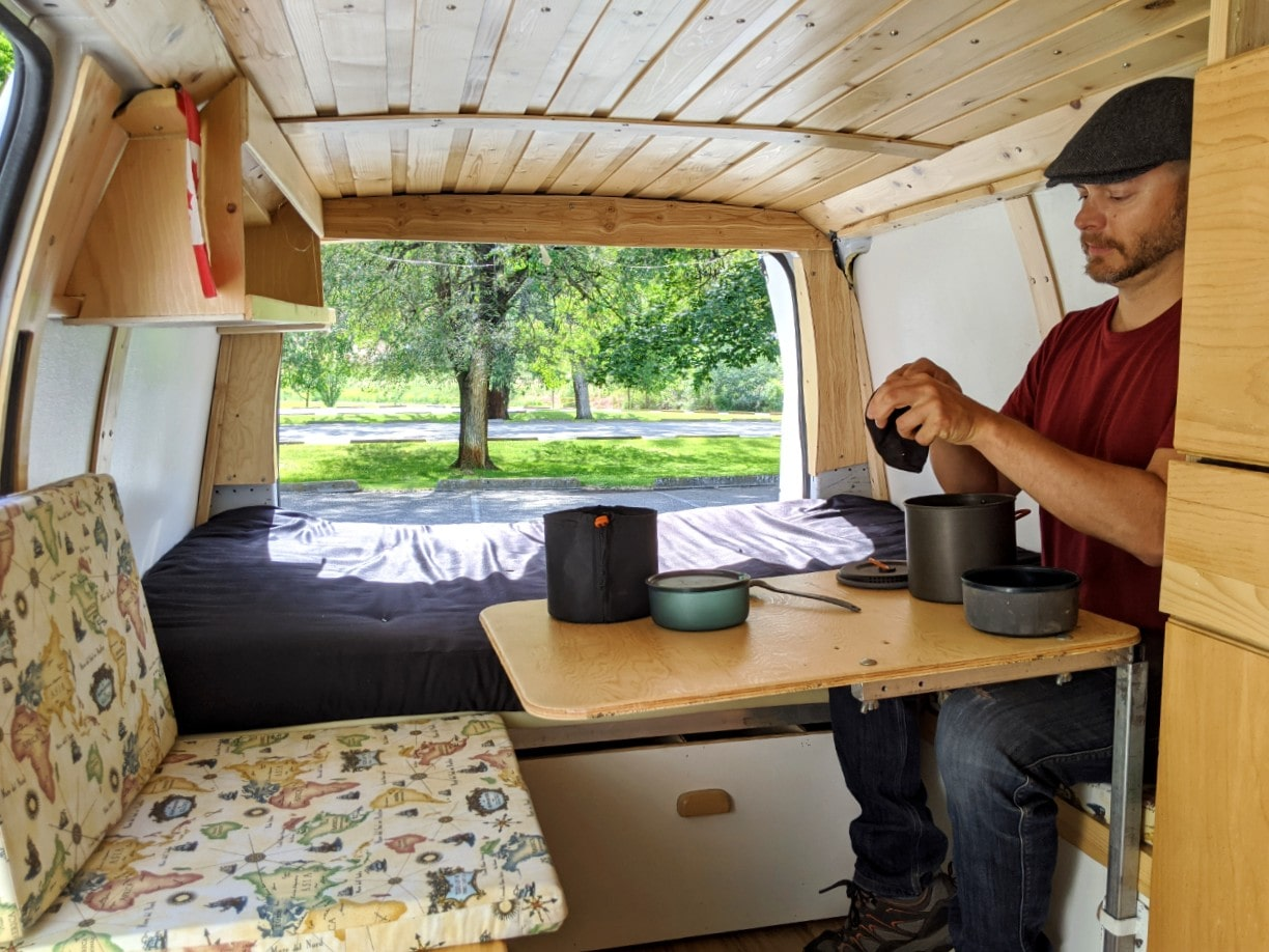 Inside DIY van conversion with table and seating out and JR sitting in van with cookware