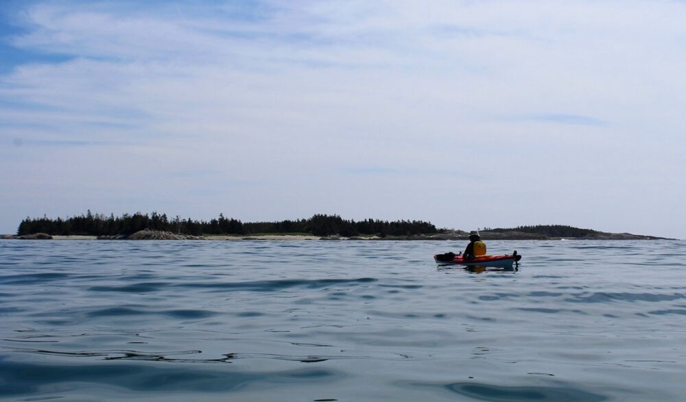 Kayak on calm ocean waters, with some of the 100 wild islands in the background