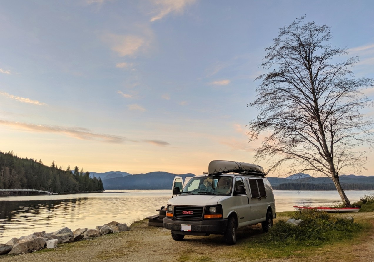 Converted GMC Savana van parked next to the coast at sunset
