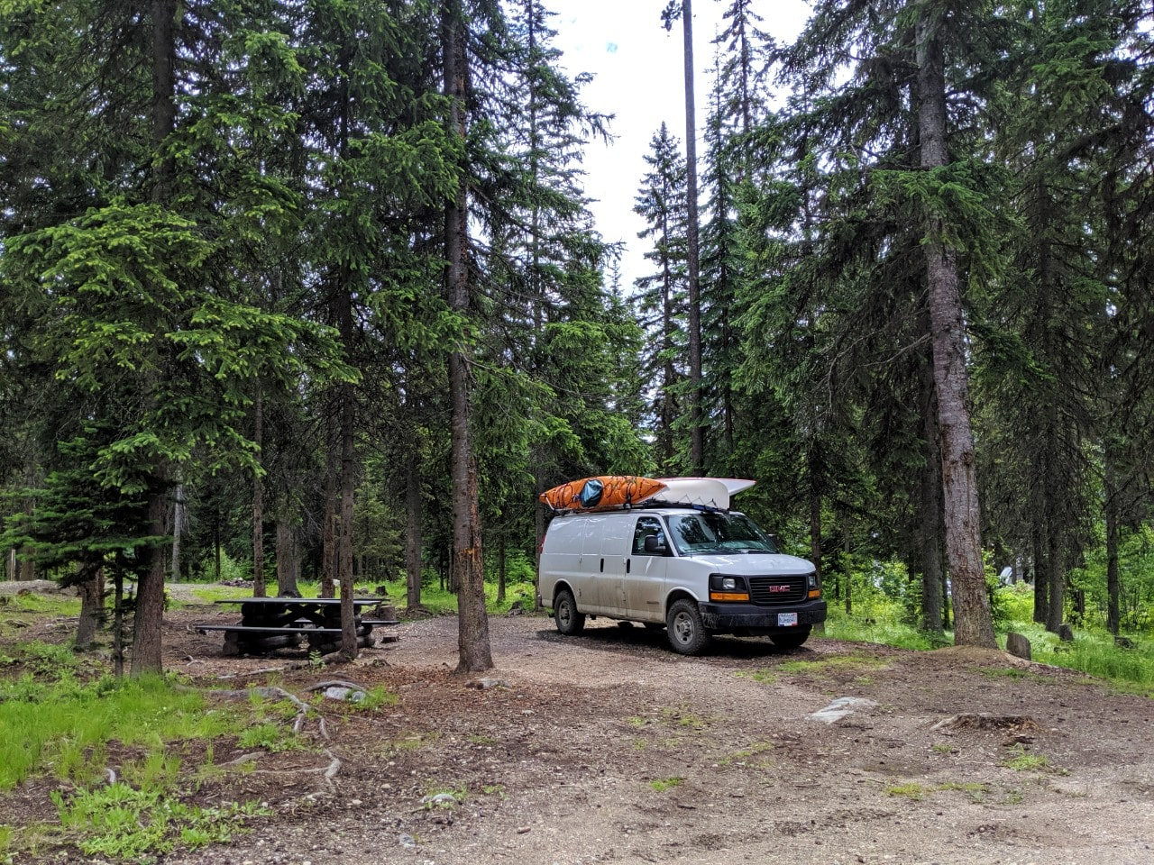 White van parked next to picnic table at free camping site in British Columbia