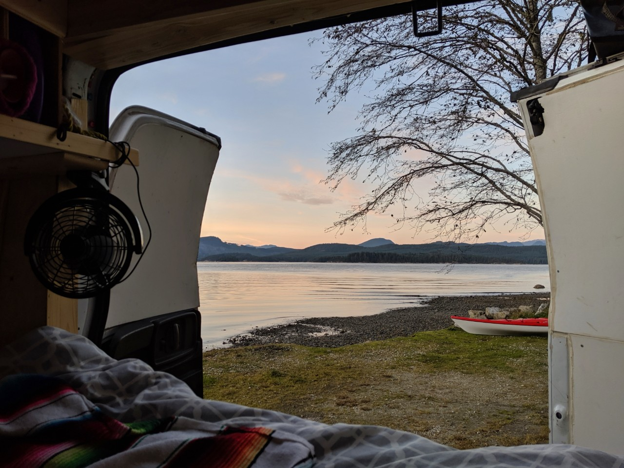 View from back of van with doors open showing coastal scenery on Vancouver Island with calm ocean and kayak on grass next to water