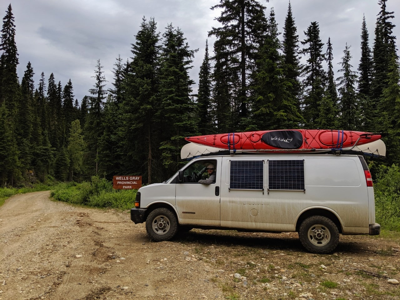 White van with kayaks and canoe on gravel road next to wooden Wells Gray Provincial Park sign