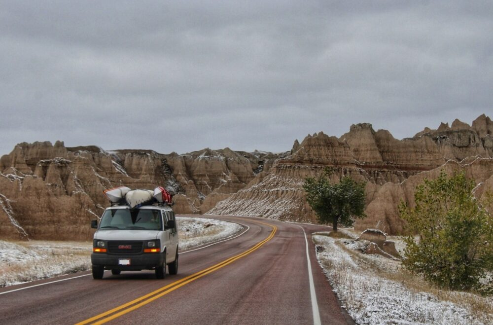 GMC Savana van driving through badlands national park, south dakota